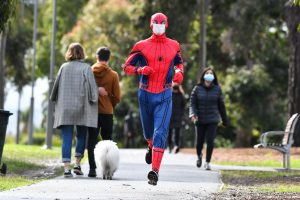 Spiderman jugging in a park wearing face mask
